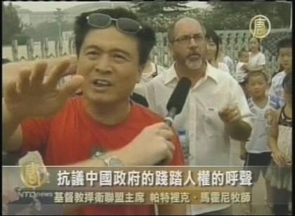 Поліцейські в цивільному перешкоджають репортерам робити зйомку християнських послідовників на площі Тяньаньмень. 7 серпня. Фото: кадри NTDTV