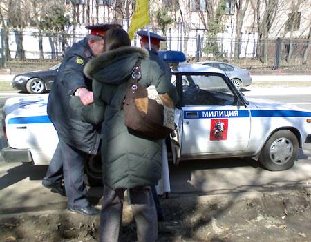 Одну из участниц митинга пытаются силой затащить в машину. Фото: Великая Эпоха