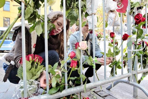 Двое 16-летних норвежцев возлагают розы в память о погибших в результате террактов Брейвика. Фото: Larsen, Haakon Mosvold/AFP/Getty Images
