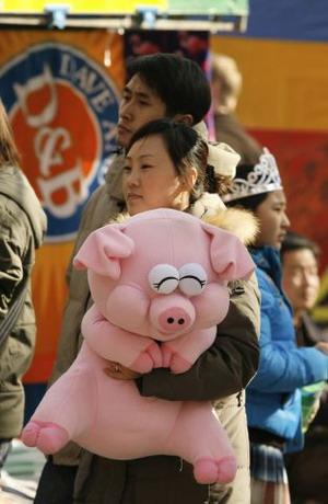 Пекин. Парк Дитань. Женщина обнимает розовую игрушку-поросенка. Фото: Peter Parks/AFP