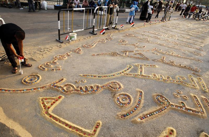 Каир, Египет, 7 июня. Протестующий пишет на песке возле главной площади столицы Тахрир надпись на арабском языке «Революция продолжается». Фото: MOHAMMED ABED/AFP/Getty Images