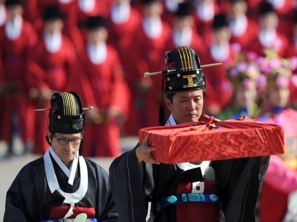 Участник торжественной церемонии держит книгу королевского архива. Фото: KIM JAE-HWAN/AFP/Getty Images
