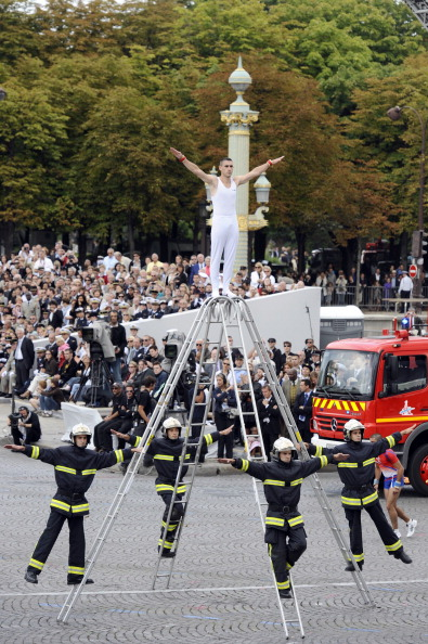Акробатические выступления французской пожарной команды на параде в Париже 14 июля 2011 года. Фото: Getty Images
