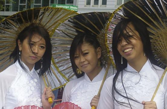 Ли-Нхи (15 лет), Ли-Ан (17 лет) и Нха-Ви (17) - вьетнамские беженцы. На заднем плане взрослые исполняли танец дракона. Фото: Чжихун Чжен/Великая Эпоха, Германия