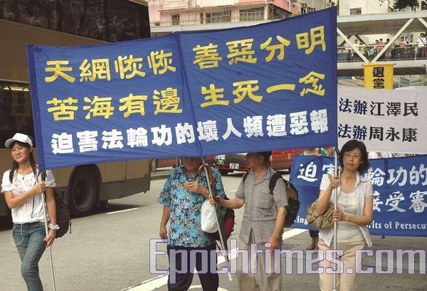 12 июля 2008г. Гонконг. Надпись на плакате: «Небесная сеть затягивается, добро и зло ясно разделились, у всех страданий есть конец». Фото: Ли Мин/ The Epoch Times