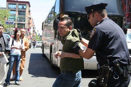 Поліцейський заарештував китайця, що напав на послідовницю Фалуньгун. Фото: The Epoch Times