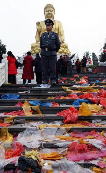 В первый день китайского Нового года после того, как разошлись паломники, рабочие собирают и сжигают огромные кучи мусора. Фото: Getty Images