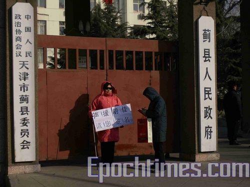 Китайська правозахисниця Чжен Мінфан напроти відділу апеляцій м. Тянцзіна збирає підписи у захист заарештованого Ху Цзя. Фото: Велика Епоха