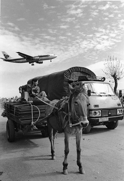 Телега, грузовик и самолёт, заходящий на посадку. Город Кунмин провинции Юньнань. 1997 год. Фото: Wu Jialin