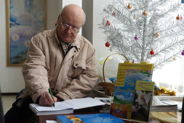 Посетитель оставляет свой отзыв о выставке после просмотра картин. Фото: Владимир Бородин/The Epoch Times