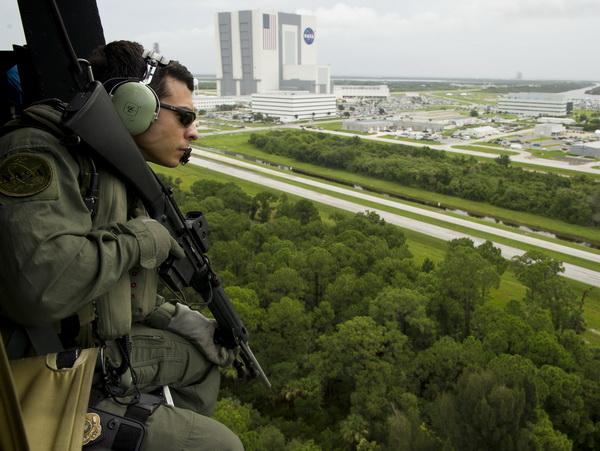 Уоррен Хинсон, сотрудник службы безопасности НАСА, наблюдает с воздуха за обстановкой возле Космического центра им. Кеннеди. Фото: Bill Ingalls/NASA via Getty Images