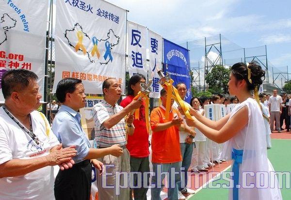 «Верховная жрица» передаёт огонь первому факелоносцу – Сэ Тухуа. 20 июля. Гонконг. Фото: Ли Мин/ The Epoch Times