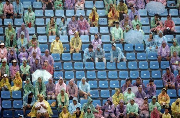 На стадіоні глядачі чекають, коли припиниться дощ, щоб подивитися перервані змагання, 10 серпня 2008 р., Пекін. Фото: BEHROUZ MEHRI/AFP/Getty Images