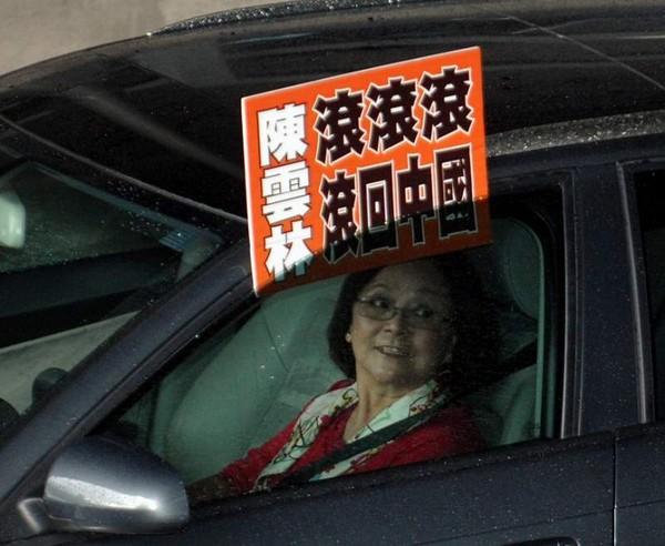 Местная жительница прикрепила плакат с надписью: «Чень Юйлинь, убирайся, убирайся, убирайся, возвращайся в Китай» к своему автомобилю и ездила возле отеля Юаньшань. Фото: ЦАН