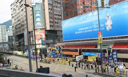 На фото показана довга колона людей, які беруть участь у заходах. Перехожі зацікавлено розглядають банери, які несуть учасники ходи. Фото: Велика Епоха