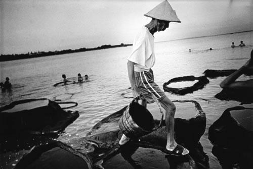 Рабочий, занимающийся выпариванием соли. Залив Янбу провинции Хайнань. 2003 год. Фото: Wan Jingchun