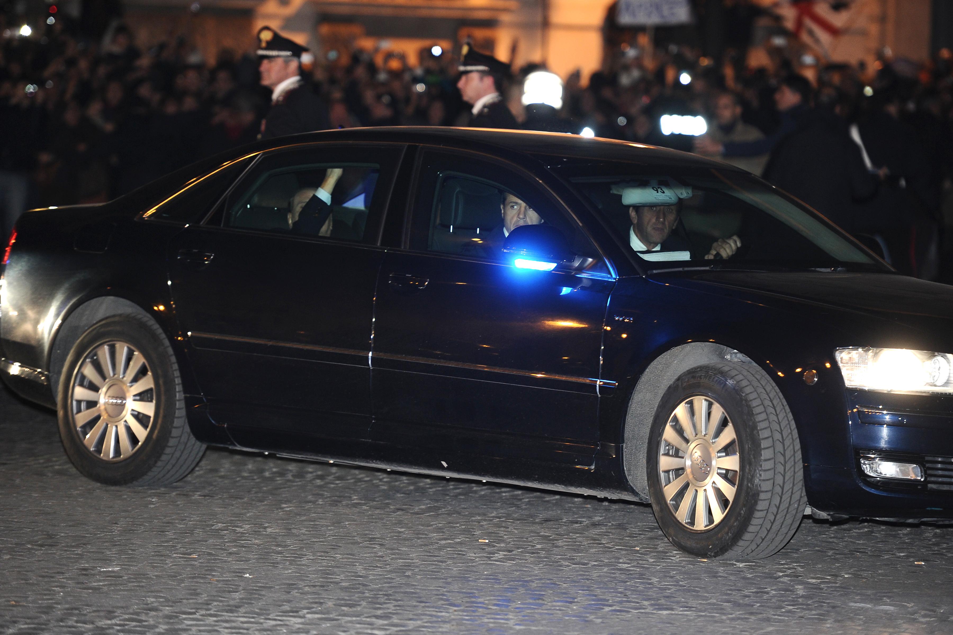 Премьер-министр Италии Сильвио Берлускони (на заднем сидении машины) прибыл в президентский дворец, чтобы официально представить прошение об отставке президенту Италии. 12 ноября 2011 года, Рим. Фото: Vincenzo Pinto/Getty Images