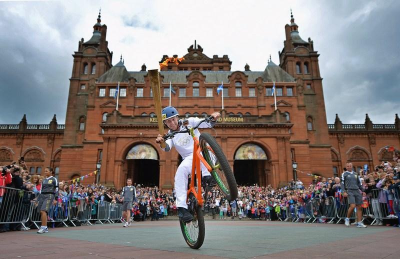 Глазго, Шотландия, 8 июня. Дэнни МакАскилл едет на трюковом велосипеде с олимпийским факелом перед зданием Художественной галереи и музея Келвингроув. Фото: Jeff J Mitchell/Getty Images