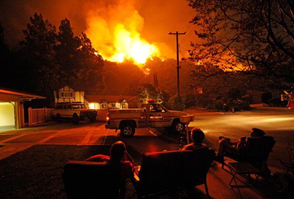 Власники будинків, які залишилися, щоб захищати свою власність, освітлені пламенем вогню спостерігають за пожежою. Фото: Kevork Djansezian/Getty Images