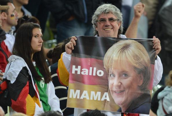 Поклонник сборной Германии держит в руках плакат с надписью «Привет Мама», адресованный канцлеру Германии Ангеле Меркель 22 июня 2012 года, Польша. Германия выиграла у сборной Греции 4—2. Фото: CHRISTOF STACHE/AFP/Getty Images