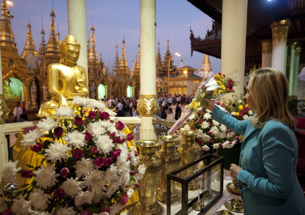 Госсекретарь США Хиллари Клинтон оставляет цветы перед статуей Будды в буддийском храме Шведагон в Янгоне. Мьянма, 1 декабря 2011 года. Фото: Saul Loeb/Getty Images