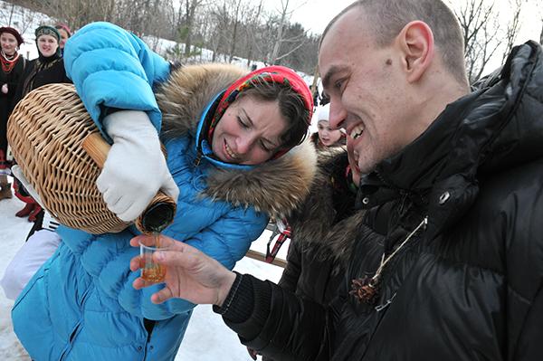 Дівчина наливає медовуху переможцю, який зняв шапку з козака. Фото: Володимир Бородін / The Epoch Times Україна