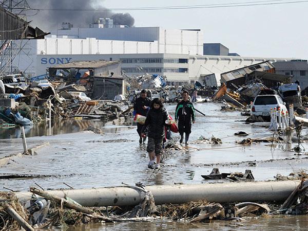 Местные жители идут по улице в Tagajo, префектура Мияги 13 марта 2011 . (KAZUHIRO NOGI/AFP/Getty Images)