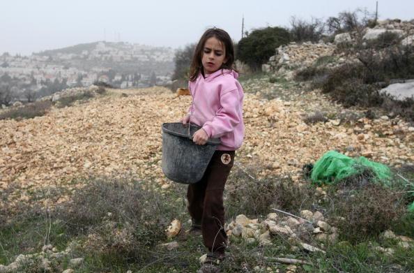 Місцеві жителі відновлюють незаконно зруйноване поселення на західному березі річки Йордан. Будівництво нового житла для ізраїльтян на окупованій території припинено на 10 місяців, з надією на відновлення переговорів з палестинцями. Фото: JACK GUEZ / AFP