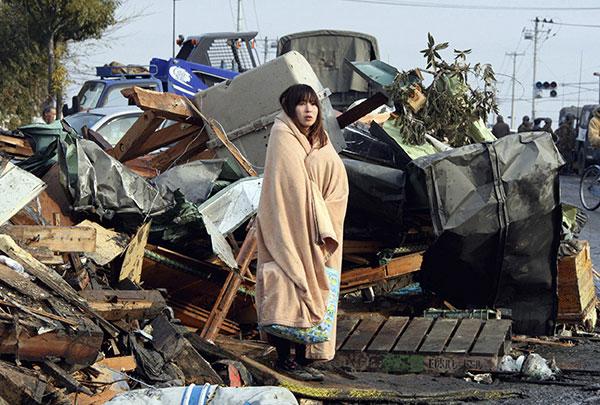 Девушка, завернутая в одеяло, смотрит на разрушеный цунами город Ishinomaki в префектуре Мияги 13 марта 2011 года. (YOMIURI SHIMBUN/AFP/Getty Images)