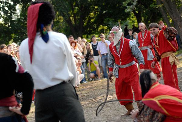 Козак с завязанными глазами хлыстом сбивает шапку с добровольца. Фото: Владимир Бородин/The Epoch Times