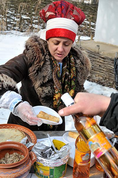 Жінка продає млинці на святкуванні Масляної в Мамаєвій слободі. Фото: Володимир Бородін / The Epoch Times Україна