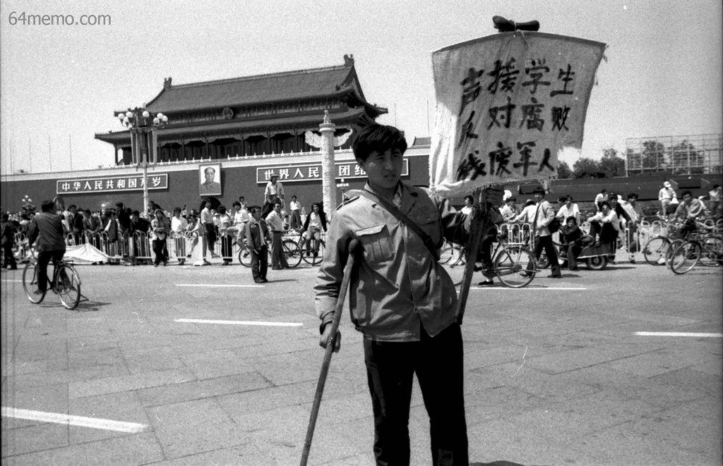 25 мая 1989 г. Военный инвалид на площади Тяньаньмэнь привязал к своему костылю плакат с надписью «Поддерживаю студентов, против коррумпированности чиновников». Фото: 64memo.com