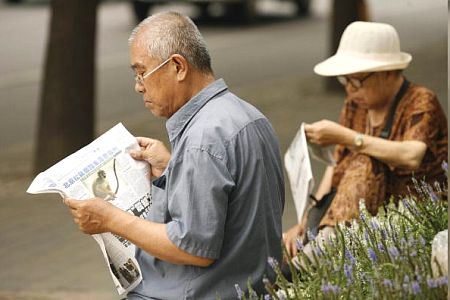Пожилые люди читающие газеты. PETER PARKS/AFP/Getty Images