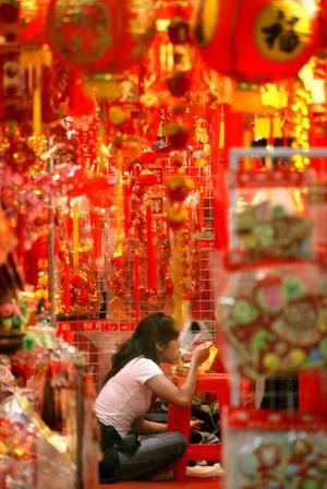 Индонезия. Джакарта. Продавщица праздничного куплета стихов на красной бумаге к Новому году. Фото: Jewel Samad/AFP