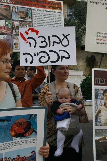 Протестувальники тримають плакат із написом 'Припинити примусову працю'. Фото: Тіква Махабад/Тhe Epoch Times