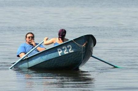 Озеро, можна і розслабитись. Чоловік сидить у човні, спокійно покурюючи цигарку, довіривши гребти жінці