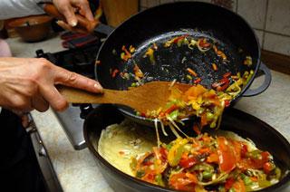В форму с тестом высыпаем тушеные овощи, добавляем базилик. Фото: Владимир Бородин/Великая Епоха