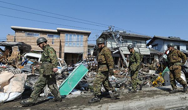 Военные патрулируют улицу покрытую мусором в Tagajo, префектура Мияги 13 марта 2011. (KAZUHIRO NOGI/AFP/Getty Images)