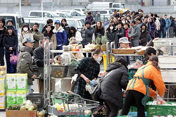 Люди в очереди, чтобы купить еду, напитки и предметы первой необходимости возле супермаркета в Shiogama, префектура Мияги 13 марта 2011. (JIJI PRESS/AFP/Getty Images)