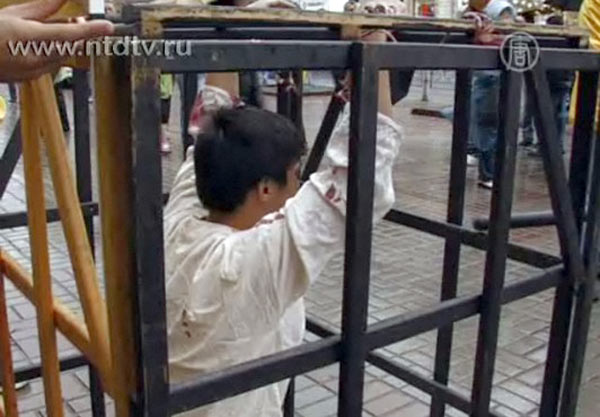 """Лі на мирній акції протесту проти тортур у Китаї. Інсценування методу тортури """"укладення в клітці"""", яка використовується у в'язницях Китаю в ході переслідування Фалуньгун. Інсценування проводиться з метою: привернути суспільну увагу до порушення прав люди"""