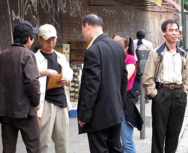 Недалеко від місця подій - району Flushing - невідомий китаєць у костюмі видає гроші активним учасникам групи підтримки компартії. Фото надане жителем Нью-Йорка