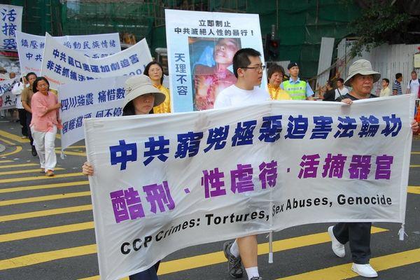 15 червня. Гонконг. Хід на підтримку 38 млн чоловік, що вийшли з КПК. Напис на плакаті: «КПК люто репресує Фалуньгун, використовуючи тортури, сексуальну наругу, видаляння органів у живих людей». Фото: Лі Чжунюань/Тhe Epoch Times