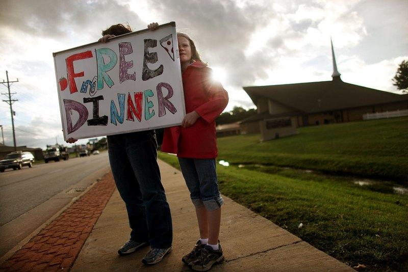 Добровольці тримають плакат з написом «Безкоштовний обід». Фото: Mario Tama/Getty Images