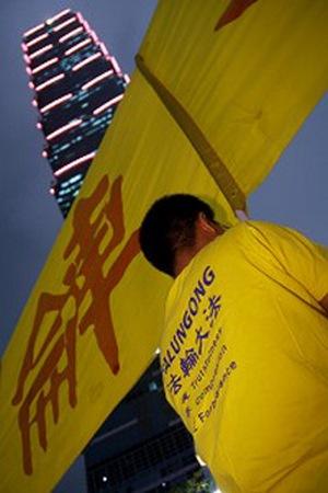 Последователи Фалуньгун напротив небоскрёба Тайбэй 101 выполняют упражнения и держат плакаты, требуя прекратить репрессии своих единомышленников в Китае. Фото: minghui.org