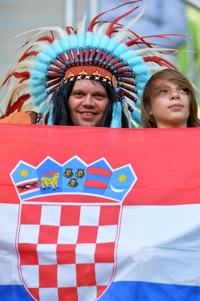 Хорватский фан в индийском головном уборе позируют с флагом своей страны на матче Хорватии против Испании 18 июня 2012 года, Арена Гданьск. Фото: GABRIEL Bouys/AFP/Getty Images