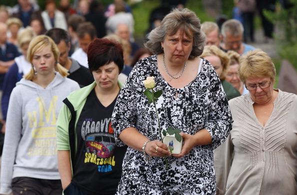 Осло, Норвегия, 25 июля. Люди держат цветы и «любовь к Осло», точно также как и тысячи людей за пределами столицы скорбят о 76 жертвах террора 22 июля 2011. Фото: Jonathan Nackstrand/Getty Images