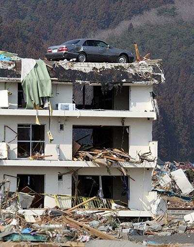 Разбитый автомобиль на разрушенном трехэтажном здании в городе Minamisanriku в префектуре Мияги 13 марта 2011 года. (JIJI PRESS/AFP/Getty Images)