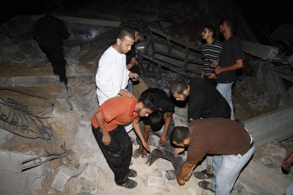 Палестинцы осматривают развалины спортивного клуба в Бейт-Лахии, который был разрушен ночью 25 августа 2011 года в результате израильской бомбежки. Фото: Mohammed Abed / Getty Images