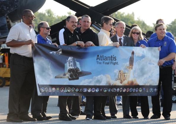 Співробітники НАСА тримають плакат, присвячений останньому польоту шатла «Атлантіс». Фото: DON EMMERT/AFP/Getty Images