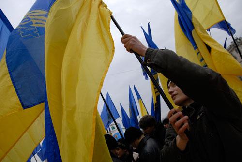 Хлопець підіймає прапор Україні на Софіївській площі. Фото: Володимир Бородін/Велика Епоха.
